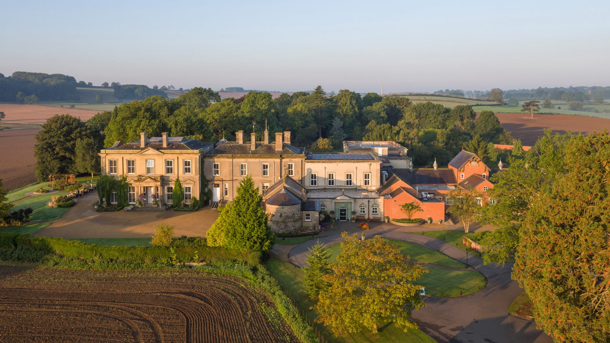 Aerial photo of Hothorpe Hall bathed in sunlight