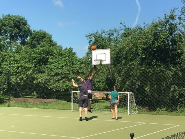 3 men playing basketball outdoors