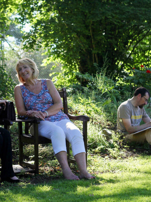 Women chatting on a garden bench with man sketching in the background