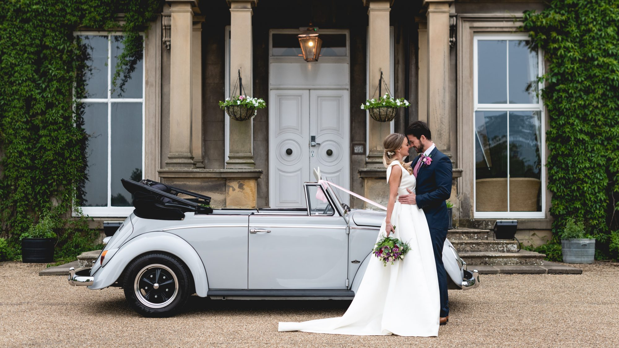 Wedding couple with car outdie Hothorpe Hall